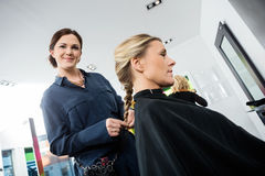 Smiling Female Hairdresser Braiding Client's Hair Royalty Free Stock Image