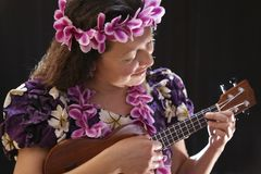 Smiling female Hawaiian girl dancing and singing with musical instruments like the ukulele. On black background Stock Photo