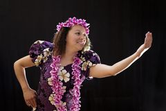 Smiling female Hawaiian girl dancing and singing with musical instruments like the ukulele. On black background Royalty Free Stock Image