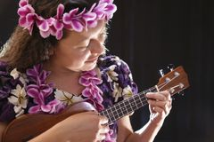Smiling female Hawaiian girl dancing and singing with musical instruments like the ukulele. On black background Royalty Free Stock Photography