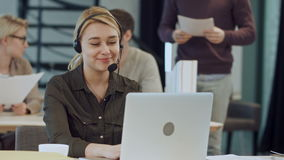 Smiling female helpline operator with headphones at her desk in the office stock video footage