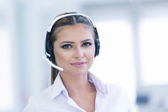 Smiling female helpline operator with headphones Stock Image