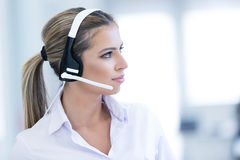 Smiling female helpline operator with headphones Stock Photo