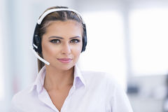Smiling female helpline operator with headphones Royalty Free Stock Photos