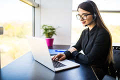 Smiling female helpline operator with headphones in office Stock Photos