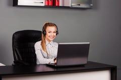 Smiling female helpline operator with headphones Royalty Free Stock Image