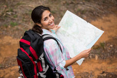 Smiling female hiker holding map in forest Stock Photo