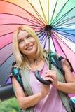 Smiling female hiker holding umbrella Royalty Free Stock Images