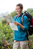 Smiling female hiker looking at map in forest Royalty Free Stock Image