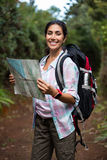 Smiling female hiker looking at map in forest Stock Photography