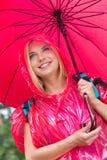 Smiling female hiker in red raincoat holding umbrella Stock Images