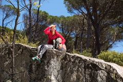 Smiling female hiker sitting at the edge of mountain and looking away Stock Photo