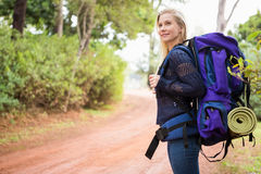 Smiling female hiker waiting by the side of the road Stock Image