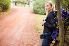 Smiling female hiker waiting by the side of the road Stock Images