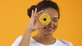 Smiling female hipster holding yellow donut front of eye, sugar dessert, snack. Stock footage stock footage