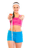 Smiling female holding apple with measuring tape Royalty Free Stock Photo