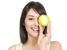 Smiling female holding a apple over eye Stock Photography
