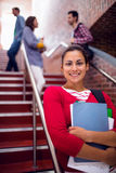 Smiling female holding books with students on stairs in college Royalty Free Stock Image
