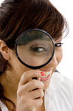 Smiling female holding magnifier close to eye Stock Photo