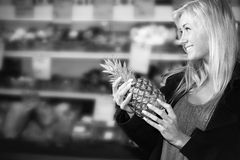 Smiling female holding pineapple in shop Stock Photography