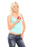 A smiling female holding a red apple Royalty Free Stock Image