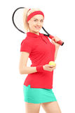 Smiling female holding a tennis racket and a ball Royalty Free Stock Image