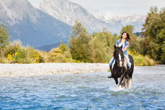 Smiling Female horse rider crossing river. In a mountainous landscape Royalty Free Stock Photo