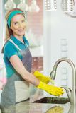 Smiling female housekeeper rinsing dishes. Female housekeeper rinsing dishes under running water in the sink in modern house, smiling at camera wearing yellow Stock Image