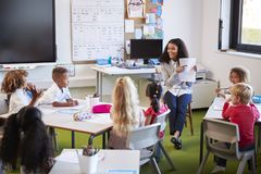 Smiling female infant school teacher sitting on a chair facing school kids in a classroom holding up and explaining a worksheet to