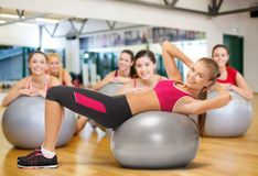 Smiling female instructor with fitness ball. Fitness, gym, exercise and health concept - young female instructor doing exercise on fitness ball infront group of Royalty Free Stock Images