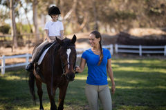 Smiling female jockey holding bridle while sister sitting on horse Stock Images