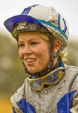 Smiling female jockey with a muddy face in the rain Stock Image