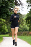 Smiling female jogger outdoors for workout. Full length portrait of smiling female jogger outdoors for workout stock image