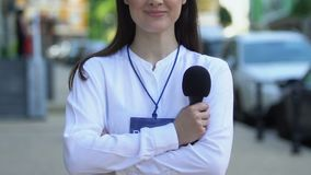 Smiling female journalist with press pass folding arms holding microphone, media. Stock footage stock footage