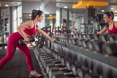Smiling female lifting dumbbell near mirror. Side view of beautiful lady in sportswear smiling and looking at mirror while leaning on rack and lifting heavy royalty free stock photography