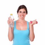 Smiling female lifting weights and water bottle Royalty Free Stock Photos