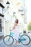 Smiling female standing next to a blue bike on a beautiful city street. Smiling female in a long white dress posing next to a blue bike on a beautiful old city Royalty Free Stock Image