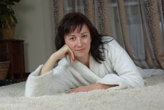 Smiling female lying on a carpet Stock Photos