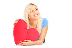 Smiling female lying down with red heart in her hands and wonder Stock Photo