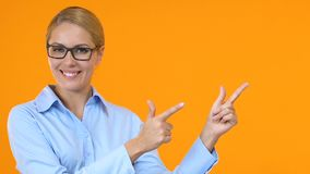 Smiling female manager pointing fingers into orange background template for text stock video