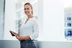 Smiling female managing director holding digital tablet Stock Photo