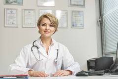 Smiling female medico doing her work. Confident doctor is sitting near desk. She looking at camera with light smile Stock Photo