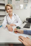 Smiling female medico at work. Benevolent doctor is sitting near desk. Modern stethoscope on her shoulders. She giving medical form to woman Stock Photos