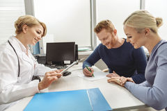 Smiling female medico at working place. Happy couple is sitting afore benevolent doctor. Man writing carefully. Medical advisor attentively looking though Stock Photo