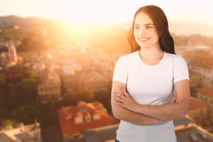 Composite image of smiling female model standing with arms crossed Stock Photo