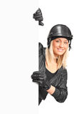 Smiling female motorcyclist holding a blank panel Stock Images
