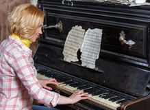 Smiling female musician playing sheet music on retro piano. Indoors Royalty Free Stock Photography