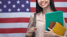 Smiling female with notebooks on American flag background, bachelor degree