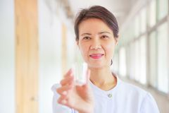 Smiling female nurse holding pill cup in her hands for patients. Professional, Specialist, Nurse, Doctor in white uniform concept Royalty Free Stock Images