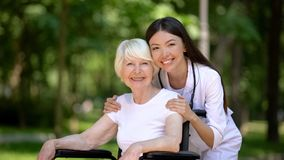 Smiling female nurse hugging disabled elderly woman and looking at camera